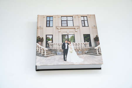 closed wedding photobook with thick pages on a white table. convenient, beautiful and long-lasting storage of photos from photo sessions. Russian names Artyom and Arina are written on the cover.