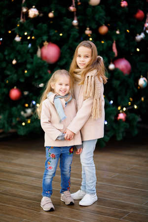 two little girls in coats and scarves near a large Christmas tree in a shopping center. walking on new year, holidays.happy childhood. shopping.