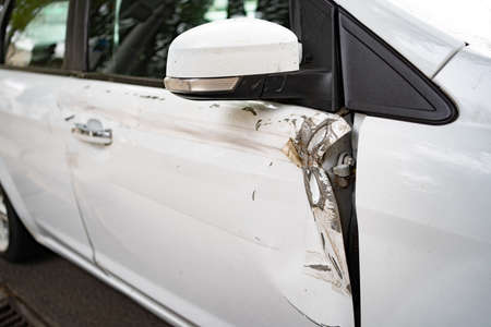white car after an accident. broken, crumpled the door of the transport. insurance against accidents.