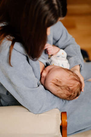 Mother breastfeeds a newborn at home on the couch. the benefits of breastfeeding 写真素材