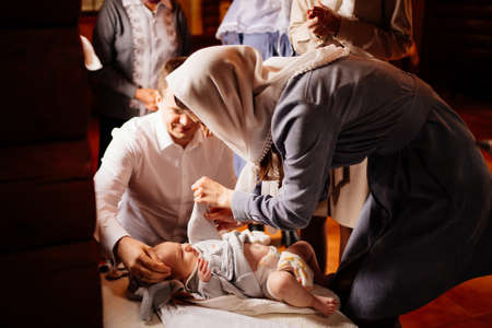 parents dress their child in the Church on a table. the ordinance of baptism. Standard-Bild