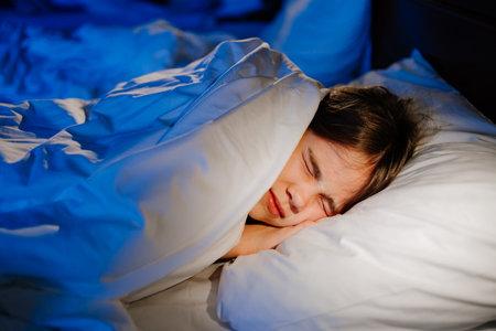A girl naps in bed, sees a nightmare in sleep. unhealthy sleep. Foto de archivo