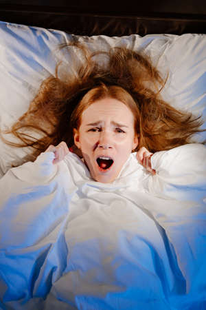 View top. a woman lies in bed under a white blanket and afraid, frightened.