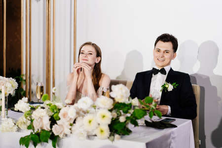 newlyweds listen to toasts, congratulations from guests and laugh Standard-Bild
