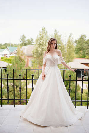 A beautiful young woman in a white wedding dress stands on the terrace. Banque d'images
