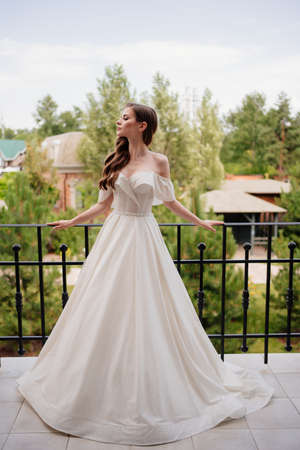 A beautiful young woman in a white wedding dress stands on the terrace.