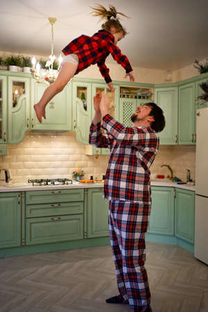 Dad throws daughter up in the kitchen.A cheerful family in red checkered pajamas