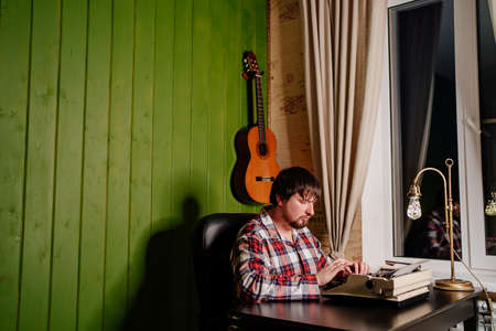 a man in plaid pajamas types on a typewriter at night in his home office.