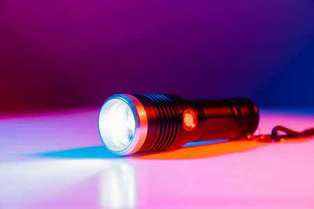 A small black flashlight in colored lighting.