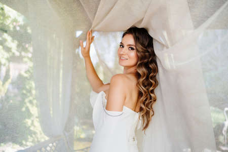 beautiful bride stand near a white curtain in a gazebo in the park. Reklamní fotografie