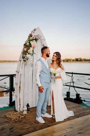 beautiful wedding ceremony by water on dock. bride and groom.