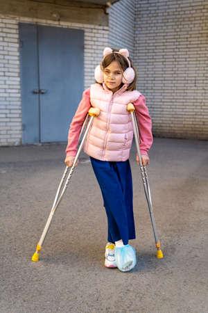 teen girl to walk on crutches. plaster on feet.