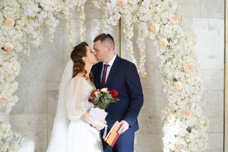 bride and groom kiss in an arch of flowers with a marriage certificate.