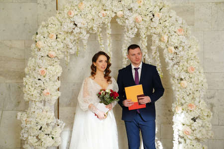 bride and groom in an arch of flowers at ceremony with a marriage certificate.