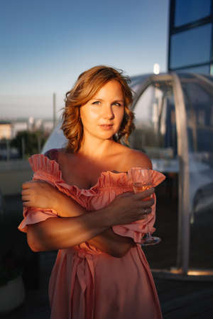 at sunset. beautiful woman in a pink dress on the roof with a glass of champagne