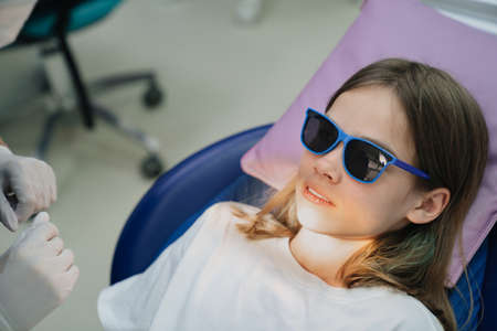 a teenage girl sits in a chair in a dental office. regular preventive visits