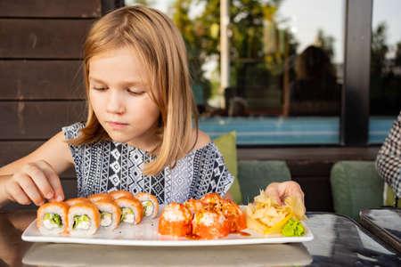 little girl in cafe restaurant eats Asian Philadelphia rolls