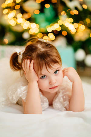 a cute girl lies under the Christmas tree. happy new year.