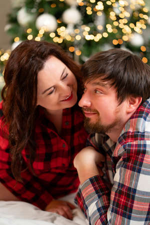in love and happy man and woman in red checkered pajamas at the Christmas tree.