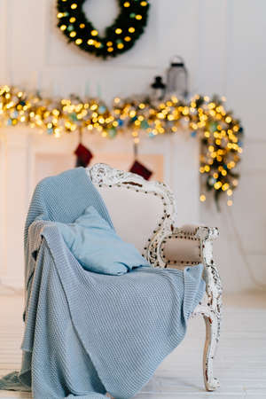 chair against the background of a fireplace with a New Years wreath and garland