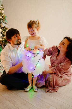 dad, mom and little daughter by Christmas tree and play with garland.