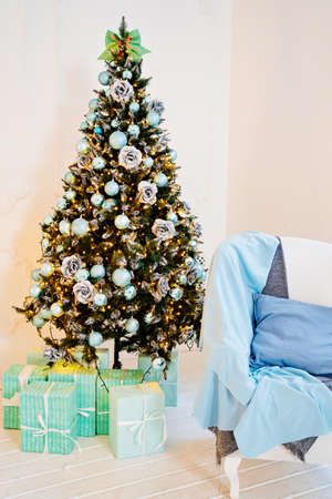 chair with blue pillow and blanket against near christmas tree with garland