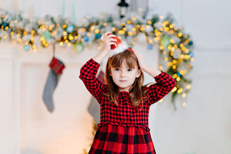 cute little girl in a red plaid dress and a cap in the New Years interior. Foto de archivo