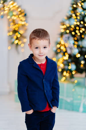 a cute little boy in a blue jacket against the background of a Christmas tree. Foto de archivo