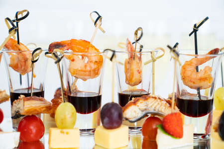 canapes of cheese with fruit, fish with tomatoes and shrimp with sauce in glass. Foto de archivo