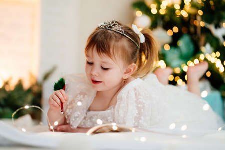 little girl writes a letter to Santa Claus under the Christmas tree.