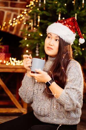 a beautiful Korean brunette drinking cocoa in a Santa Claus hat Foto de archivo