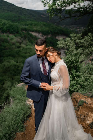 a beautiful hugging couple of newlyweds in a wedding ceremony in the mountains Foto de archivo