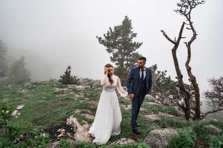 newlyweds walk holding hands in misty mountain forest. wedding on trip Foto de archivo