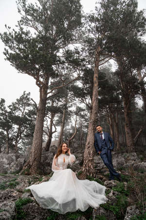 fun bride and groom in a mysterious misty mountain forest. honeymoon