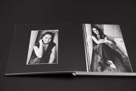 open photobook from a photo shoot of an attractive woman on a black background.
