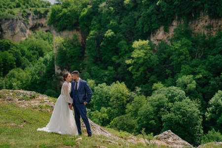 beautiful newlyweds against backdrop of mountain forest. wedding in mountains.