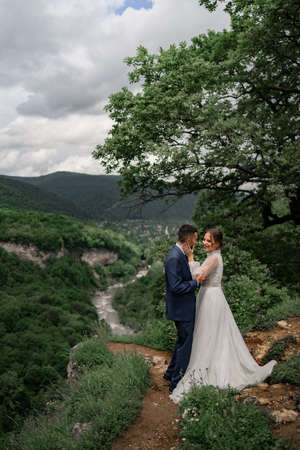 a beautiful hugging newlyweds in a wedding ceremony in the mountains Foto de archivo