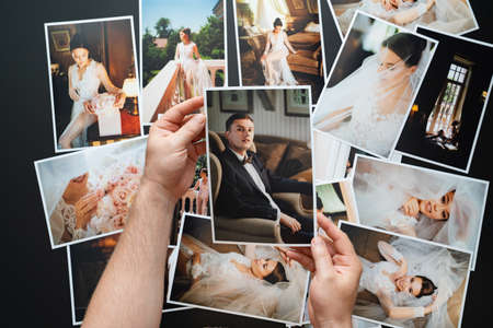 hands lay out wedding photos. the result of the photographers work at wedding.