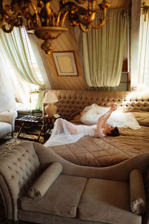 a bride in a lace robe lies in bed. morning before the wedding.