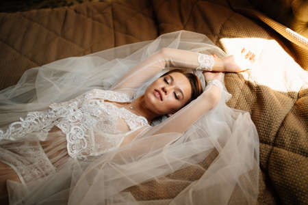 beautiful bride in a lace robe lies in bed on a veil. morning before the wedding