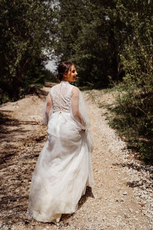 bride in wedding dress walks along mountain path between trees. view from back.