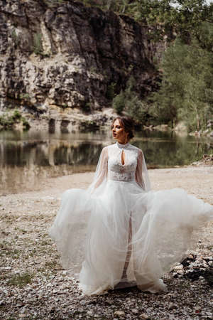attractive woman in white wedding dress at photo shoot on shore of mountain lake Foto de archivo