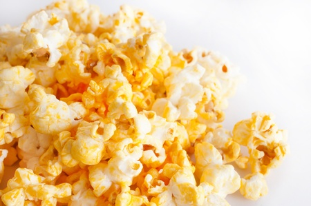 Salted popcorn grains on the white background photo