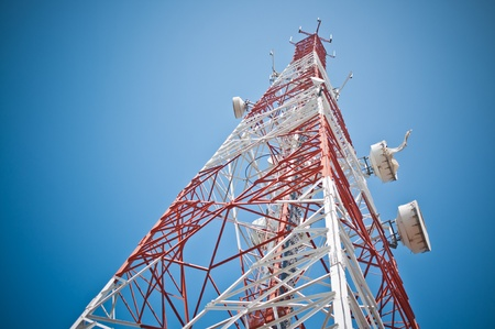 Anténa komunikace budovy a modrou oblohu