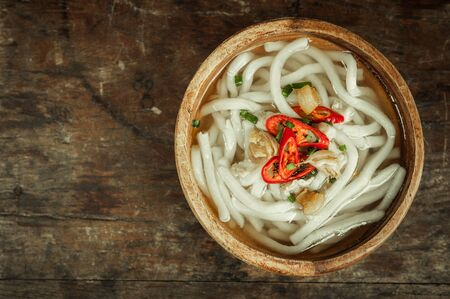 gusto: udon noodle in wood bowl on wooden floor background