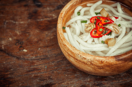 gusto: closeup of udon noodle in wood bowl on wooden floor background Stock Photo