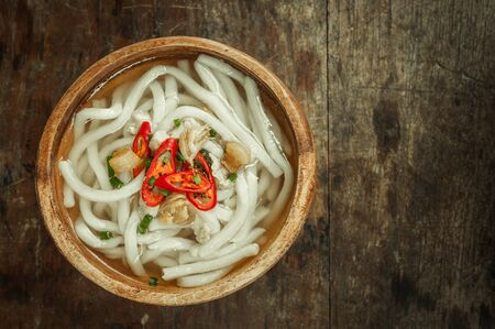 wood floor background: closeup of udon noodle in wood bowl on wooden floor background Stock Photo