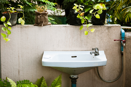 vintage of washbasin and grunge wall in the garden