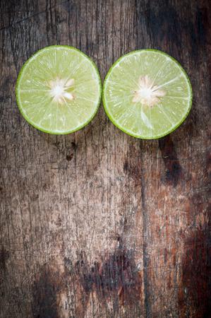 lemon slices: Green Lemon cut on wooden background