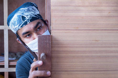 wood planer: Young male carpenter take a planer with wood in workshop